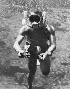 Early scuba diver with underwater camera